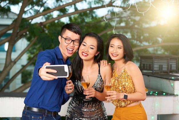 パーティーで美しい女性の友人と自分撮りをしている陽気な若いベトナム人実業家
