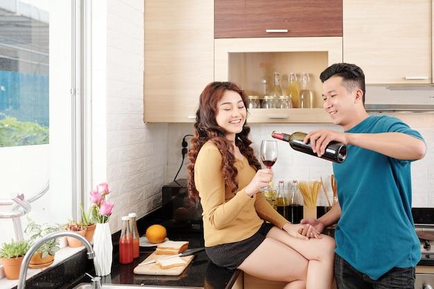 쾌활한 젊은 베트남 부부는 집에서 부엌에서 와인을 마시고 저녁 식사를 요리합니다.