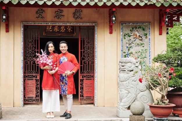 Веселая молодая вьетнамская пара в традиционных платьях стоит у дверей храма с цветущими персиковыми ветвями и бумажным веером