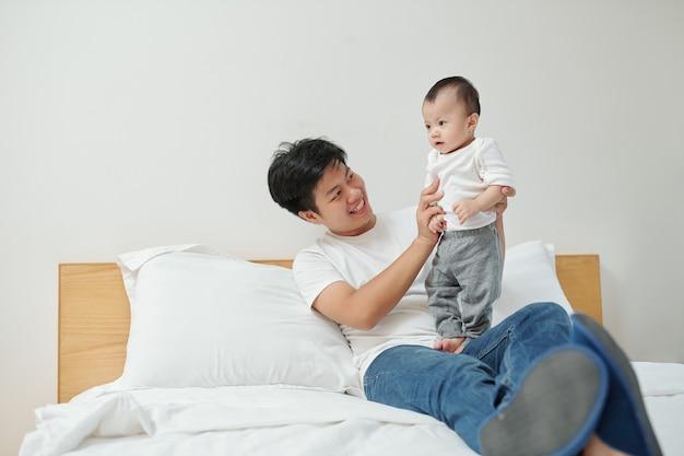 쾌활한 젊은 베트남 남자가 침대에 앉아 사랑스러운 작은 딸과 함께 연주