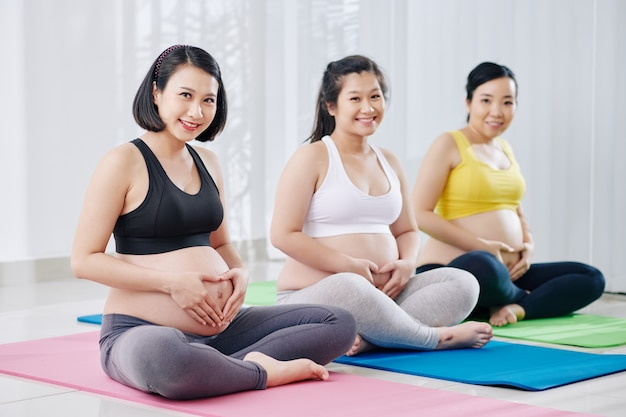 Cheerful young vietnamese women sitting in lotus position and touching their bellies after practicing yoga in class