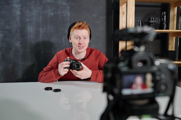 Cheerful young vlogger by desk holding new photocamera while talking about its characteristics during video shooting in studio