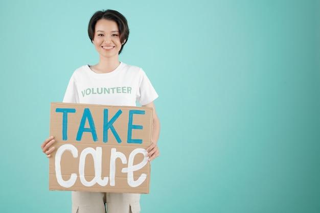 Веселый молодой волонтер общественного центра пожертвований держит плакат заботы