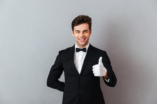 Cheerful young waiter standing isolated showing thumbs up.