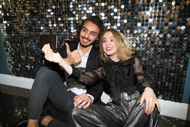 Веселая молодая хорошо одетая пара делает селфи, сидя у сверкающей стены в ночном клубе на вечеринке