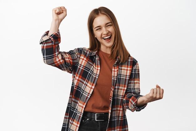 쾌활한 젊은 여성은 목표 성공, 기쁨의 비명, 주먹 펌프, 팀 응원, 성취 획득, 상, 승리 및 승리, 흰 벽