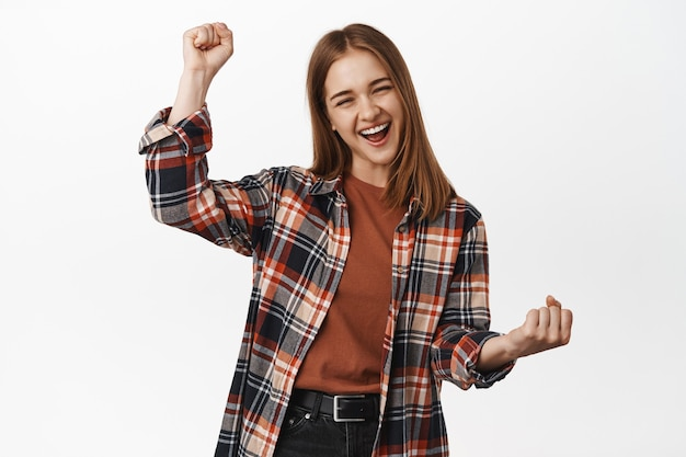 Cheerful young woman achieve goal success, scream from joy, fist pump, rooting for team, gain achievement, prize, winning and triumphing, white wall