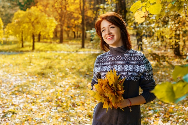 Cheerful young woman in autumn park smiling on a sunny day.