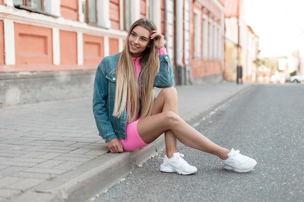 매력적인 핑크 스포츠 정장에 흰색 스 니 커 즈에 트렌디 한 데님 재킷에 쾌활 한 젊은 여자 금발은 밝은 여름날에 건물 근처 도로에 쉬고 있습니다. 야외에서 앉아 미국 여자 모델