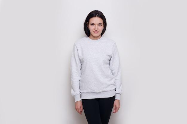 明るい灰色のセーター、白い背景で隔離の陽気な若い女性ブルネット。テキスト用のスペース。