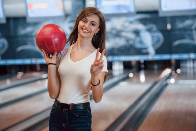 Giovane donna allegra in abbigliamento casual che tiene palla da bowling rossa nel club