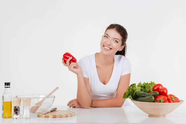 Cheerful young woman cooking with vegetables