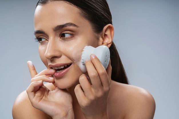 화장품 기기로 얼굴 청소를 하는 쾌활한 젊은 여성