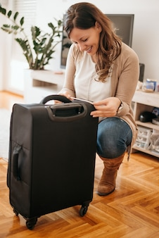 Cheerful young woman doing inspection of luggage. measuring luggage before going on holiday.
