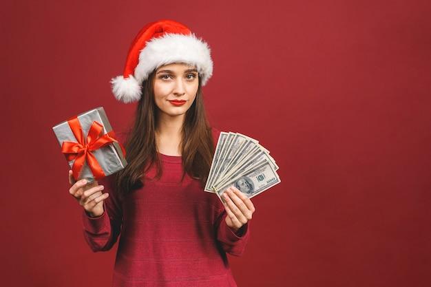 陽気な若い女性はお金と驚きのギフトボックスを持って立っているクリスマス帽子をかぶっている赤いセーターを着ています。