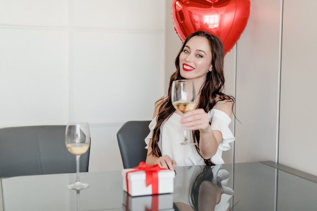 Cheerful young woman drinking wine from glass at home with heart shaped balloons