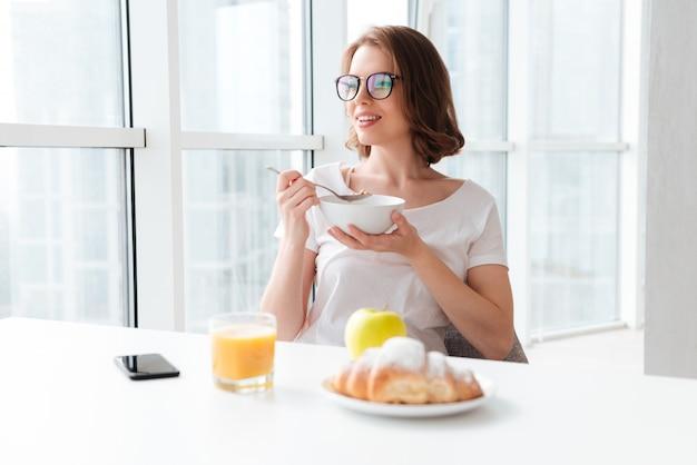 Веселая молодая женщина ест кукурузные хлопья