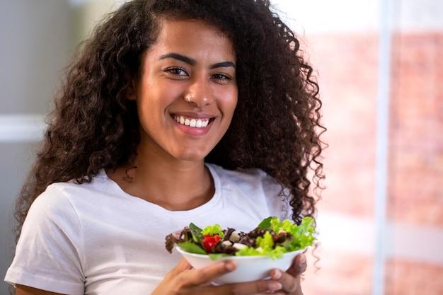 가정 부엌에서 야채 샐러드를 먹는 쾌활 한 젊은 여자.