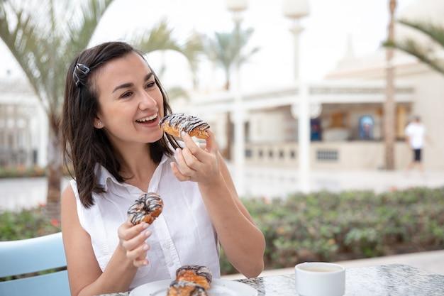 屋外テラスでドーナツと朝のコーヒーを楽しんでいる陽気な若い女性。休暇とレクリエーションの概念。