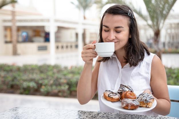 야외 테라스에서 도넛과 모닝 커피를 즐기는 쾌활 한 젊은 여자. 휴가 및 레크리에이션 개념.