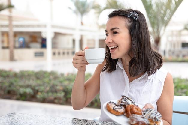 屋外テラスでドーナツと朝のコーヒーを楽しんで陽気な若い女性