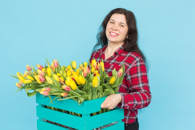 파란색 배경 위에 튤립 상자와 쾌활 한 젊은 여성 꽃집