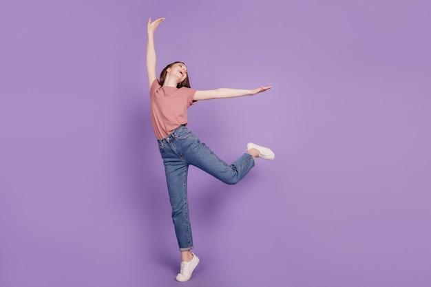 紫色の背景に分離されたダンスのポーズをとって陽気な若い女性の女の子