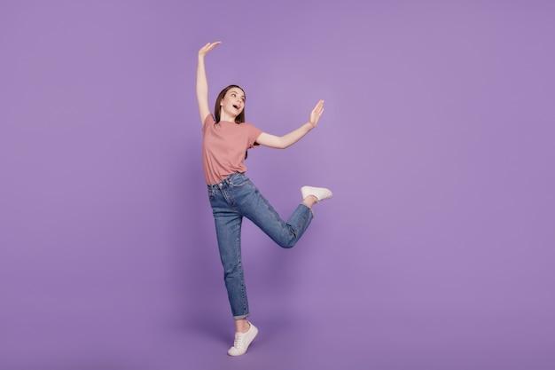 ダンスのポーズをとって陽気な若い女性の女の子は、紫の背景に分離された空のスペースに見えます