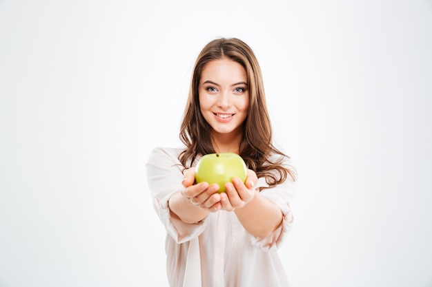 白い壁に隔離された正面にリンゴを与える陽気な若い女性
