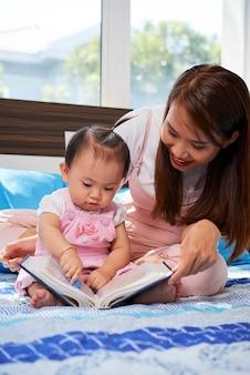 그녀를 즐겁게하기 위해 사진과 함께 작은 딸 책을주는 쾌활한 젊은 여자