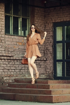 Веселая молодая женщина выходит из здания