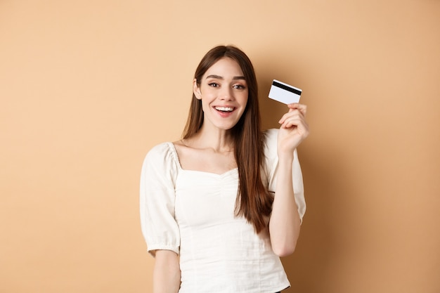 Cheerful young woman got her plastic credit card and smiling satisfied standing pleased on beige bac...
