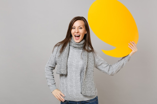 Cheerful young woman in gray sweater, scarf holding yellow empty blank say cloud, speech bubble isolated on grey background. healthy fashion lifestyle, people sincere emotions, cold season concept.