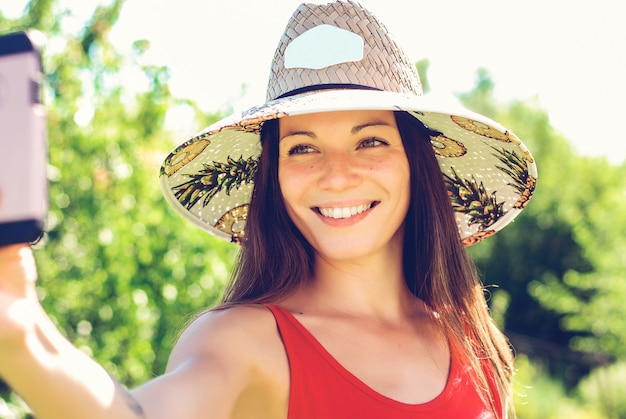 Cheerful young woman in hat taking selfie with mobile phone on summer resort