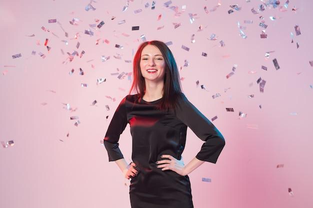 Веселая молодая женщина развлекается, пока на нее падает конфетти