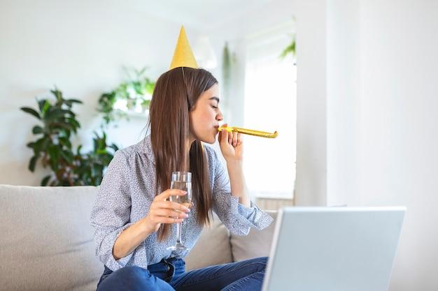 ビデオ通話で友人と誕生日のお祝いイベントを持っている陽気な若い女性。