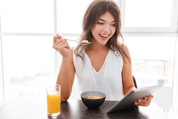 아침을 먹고 집에서 휴대전화를 사용하는 쾌활한 젊은 여성