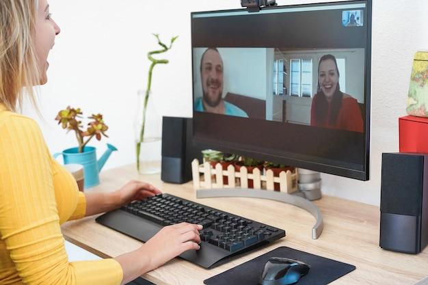 Веселая молодая женщина, имеющая видеозвонок на компьютере с друзьями - сосредоточиться на