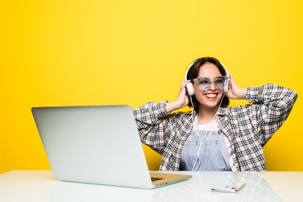Cheerful young woman in headphones dancing to music while sitting in front of computer