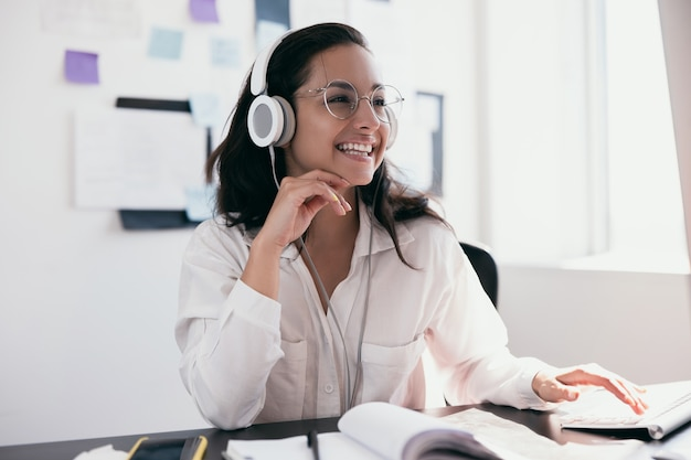 Cheerful young woman in headphones enjoying listening to music and smiling