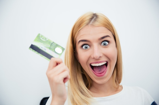 Cheerful young woman holding bank card