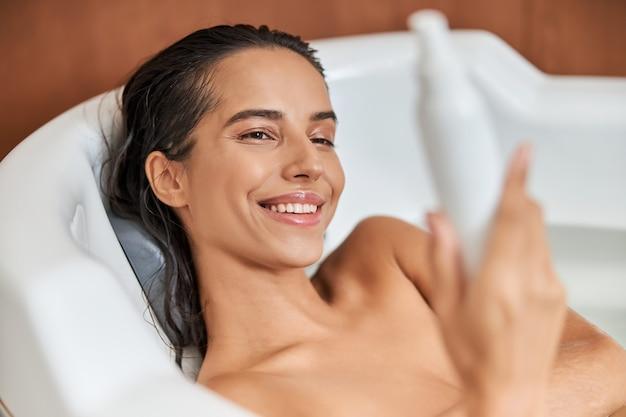 入浴中にローションのボトルを保持している陽気な若い女性