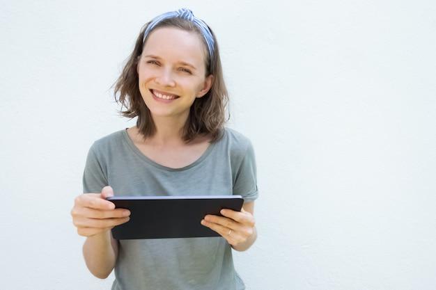 Giovane donna allegra che tiene dispositivo digitale