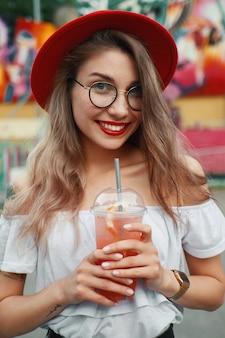 Giovane donna allegra che tiene un drink mentre sorridendo