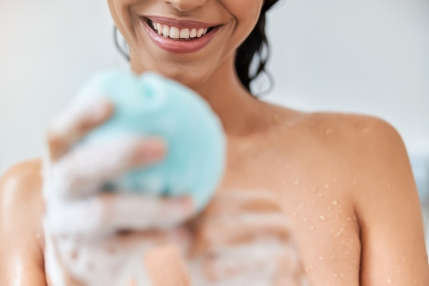 Cheerful young woman holding exfoliating loofah sponge