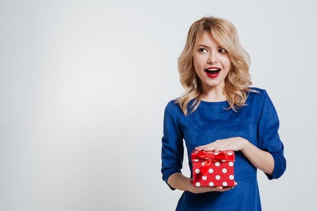흰 벽에 선물 상자를 들고 쾌활 한 젊은 여자