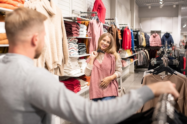 Cheerful young woman holding hangers with pink pullover by chest while looking at her boyfriend in clothing department