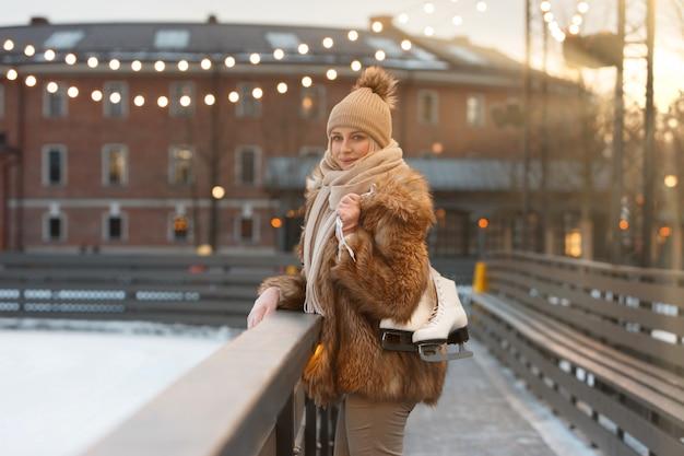 凍るような日にアイススケートを保持している陽気な若い女性