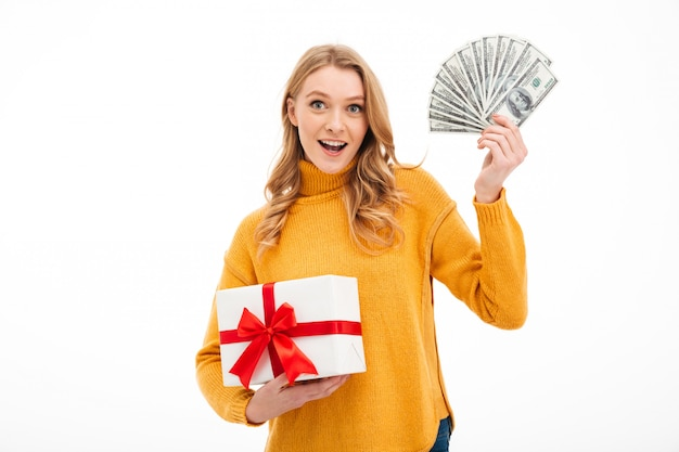 Cheerful young woman holding money and surprise gift box.