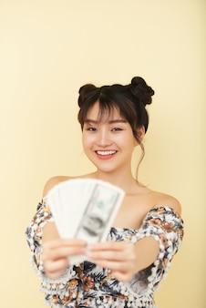 お金を保持している陽気な若い女性